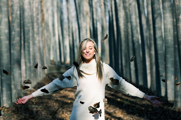 Beautiful blonde Ukrainian girl with falling leaves in the autumn park