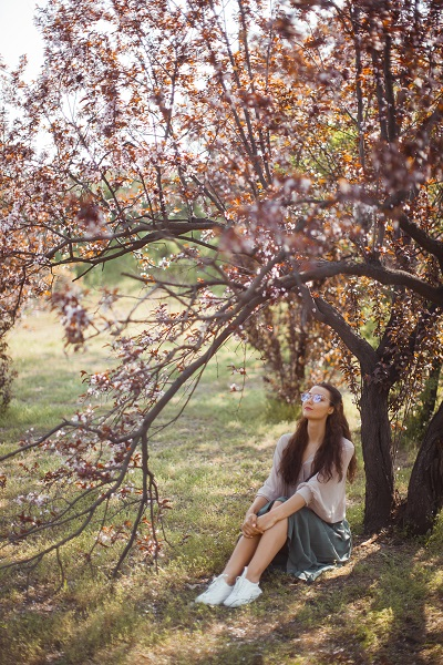 Ukrainian girl outdoors in the park near spring blossom tree wearing glasses
