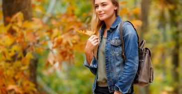 Beautiful Ukrainian woman in the autumn park walking alone