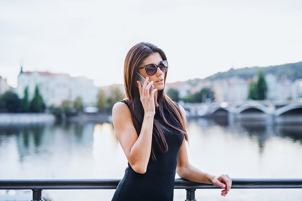 Beautiful Ukrainian lady in a black dress standing by a river and making a call