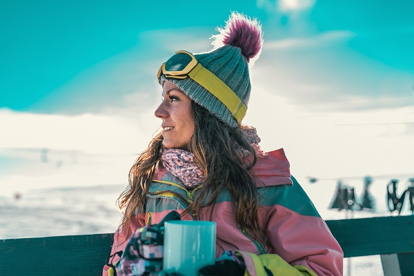 Ukrainian woman with cup of coffee enjoying the cold winter day on the mountains