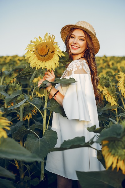Beautiful and stylish Ukrainian girl wearing a nice hat in the with sunflowers