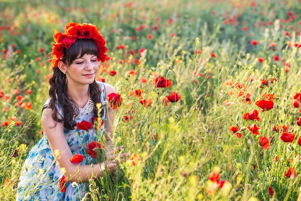 Beautiful Ukrainian lady looking at the flowers and touching them on the poppy field