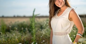 Beautiful happy Ukrainian woman standing alone and smiling outdoors