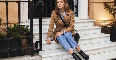 Young pensive Ukrainian lady in a trench coat and jeans dreamily looking at the camera