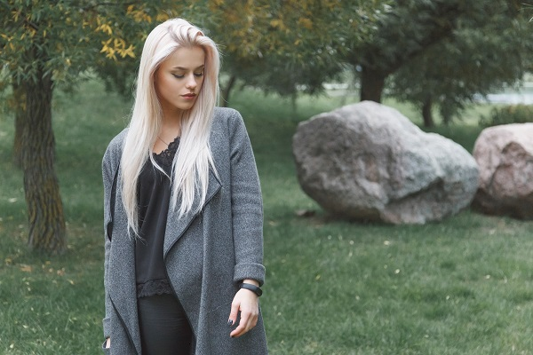 Young blond-haired Ukrainian woman in a gray coat with smart bracelet standing outdoors