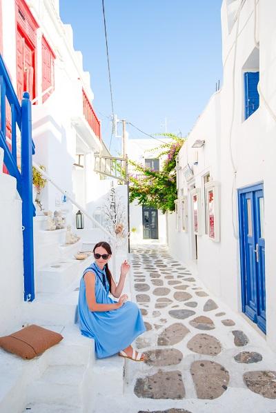 Ukrainian female tourist walking along the deserted streets of the Greek village