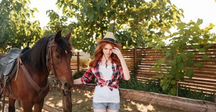 Young Ukrainian woman wearing a hat walking with her horse in the village garden