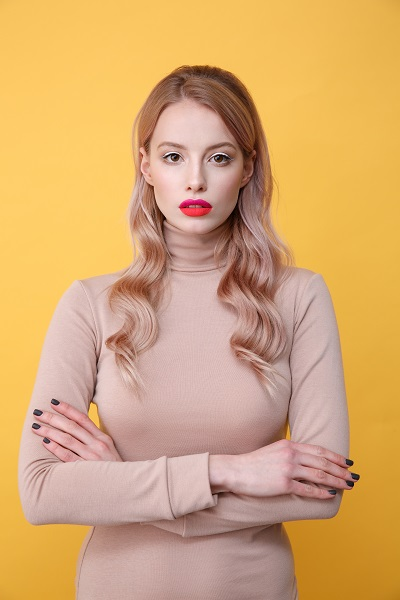 Concentrated young Ukrainian blonde lady with bright makeup lips watching in the camera