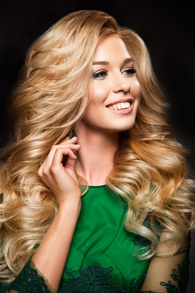 Portrait of elegant sexy Ukrainian blonde woman with a long curly hair and glamour makeup