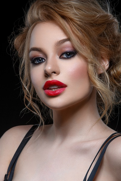 Beautiful young Ukrainian girl in a black classic dress wearing red lipstick all over