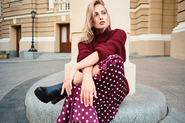 Gorgeous stylish Ukrainian blond girl in a knitted sweater sensually looking away posing outdoors