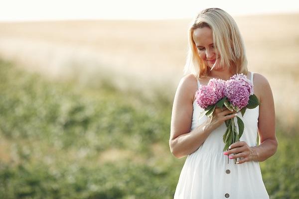 Beautiful elegant Ukrainian girl in an autumn field walking with a bouquet of flowers alone