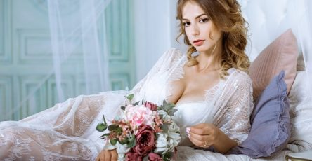 Beautiful sexy Ukrainian lady wearing an elegant white robe with a bouquet of flowers