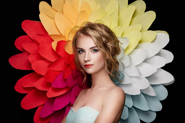Beautiful Ukrainian woman wearing sexy white dress on the background of a large flower