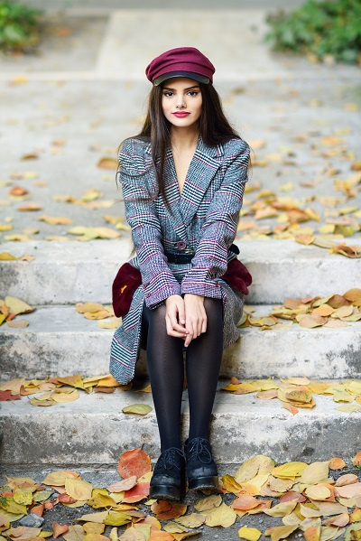 Young beautiful Ukrainian girl wearing a winter coat and cap sitting on the steps full of autumn leaves