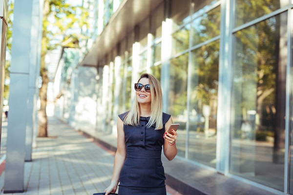 Happy young successful Ukrainian businesswoman walking with her phone in a hand on the street