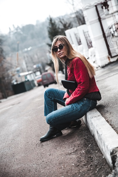 Beautiful stylish young Ukrainian woman sitting on a road with her sunglasses on while wearing jeans with the boots