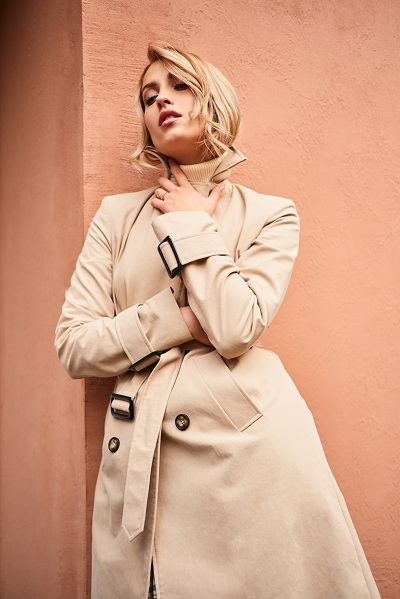 Beautiful stylish blond Ukrainian girl in a beige trench coat sensually posing outdoor touching her own neck